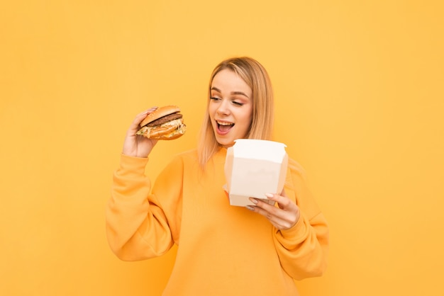 Uśmiechnięta Dziewczyna W Pomarańczowych Ubraniach Jest Zapakowana Z Burgerem W Ręce Na żółtym Premium Zdjęcia