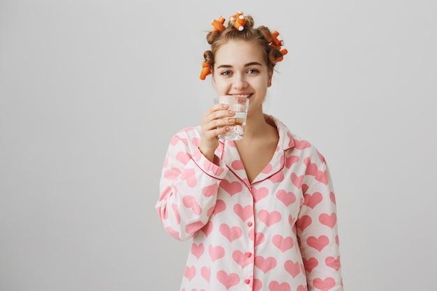 Uśmiechnięta Dziewczyna W Wodzie Pitnej Piżamy, Za Pomocą Lokówek Darmowe Zdjęcia