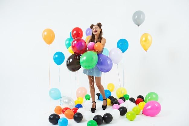 Uśmiechnięta Dziewczyna Wygląda Szczęśliwy, Trzymając Kilka Dużych Balonów Darmowe Zdjęcia