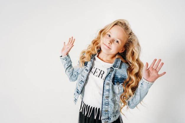 Uśmiechnięta Dziewczyna Z Kręconymi Włosami W Dżinsowej Kurtce I Czarnej Spódnicy Tutu Z Podniesionymi Rękami Na Białym Na Białym Tle Premium Zdjęcia