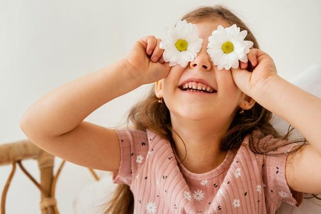 Uśmiechnięta Dziewczynka Bawi Się Wiosennymi Kwiatami Zasłaniającymi Oczy Darmowe Zdjęcia
