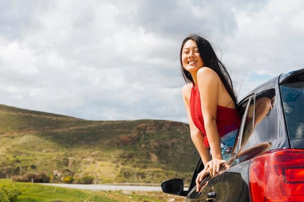 Uśmiechnięta etniczna kobieta patrzeje z samochodowego okno Darmowe Zdjęcia