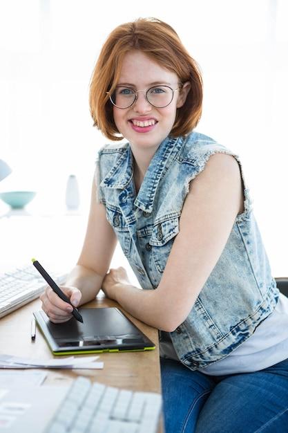 Uśmiechnięta hipster kobieta przy biurku, pisząc na cyfrowym tablecie rysunkowym Premium Zdjęcia