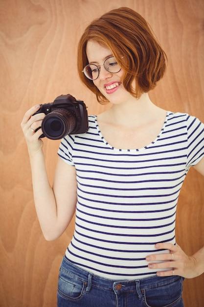 Uśmiechnięta hipster kobieta trzyma aparat cyfrowy Premium Zdjęcia