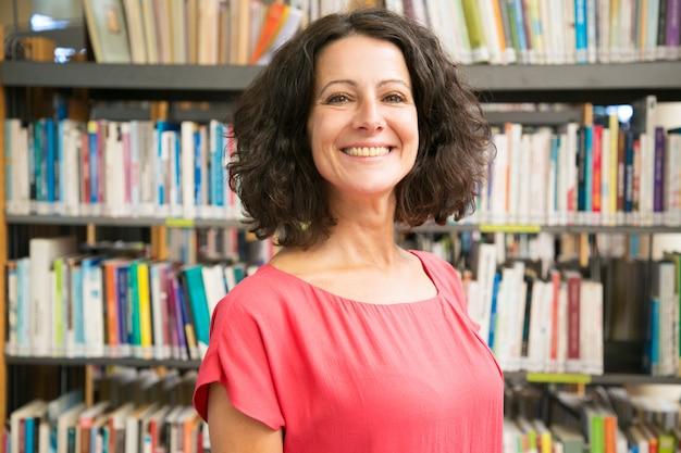 Uśmiechnięta kaukaska kobieta pozuje przy biblioteką publiczną Darmowe Zdjęcia