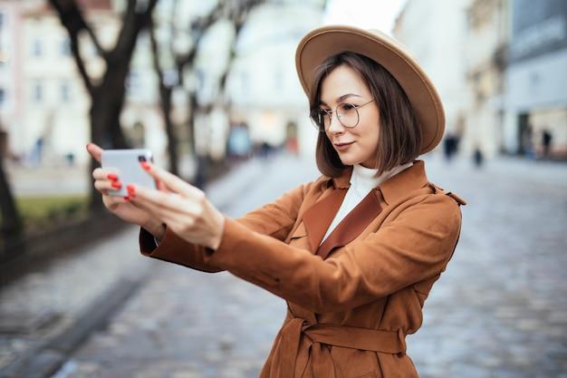 Uśmiechnięta Kobieta Bierze Fotografię Na Jej Telefonie W Jesień Dniu Outside Darmowe Zdjęcia