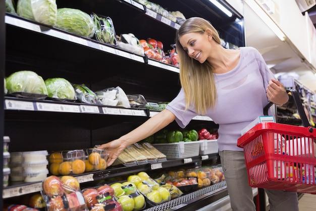Uśmiechnięta kobieta bierze warzywa w nawie Premium Zdjęcia