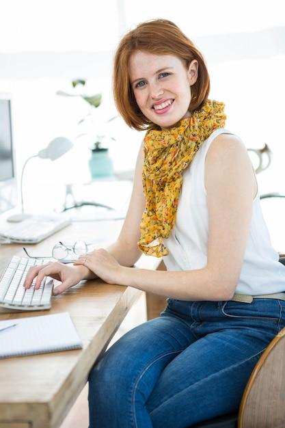 Uśmiechnięta kobieta biznesu hipster siedzi przy biurku, ubrany w szalik Premium Zdjęcia