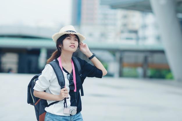 Uśmiechnięta Kobieta Chodzi Outdoors, Młoda Dama Podziwia Widok Miasta Z Przejściem I Budynkami W Tle. Darmowe Zdjęcia