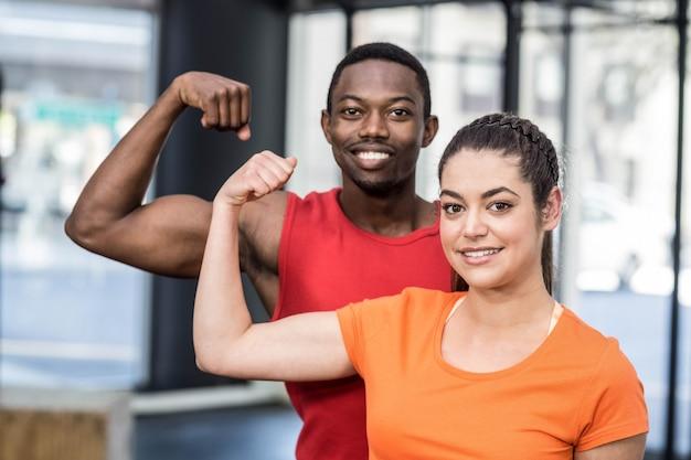 Uśmiechnięta kobieta i mężczyzna kontraktuje bicepsy przy crossfit gym Premium Zdjęcia