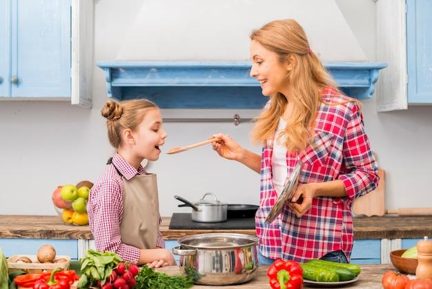 Uśmiechnięta kobieta kosztuje jedzenie jej córka z drewnianą łyżką w kuchni Darmowe Zdjęcia