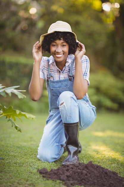 Uśmiechnięta Kobieta Kuca W Ogródzie Trzyma Jej Kapelusz Premium Zdjęcia