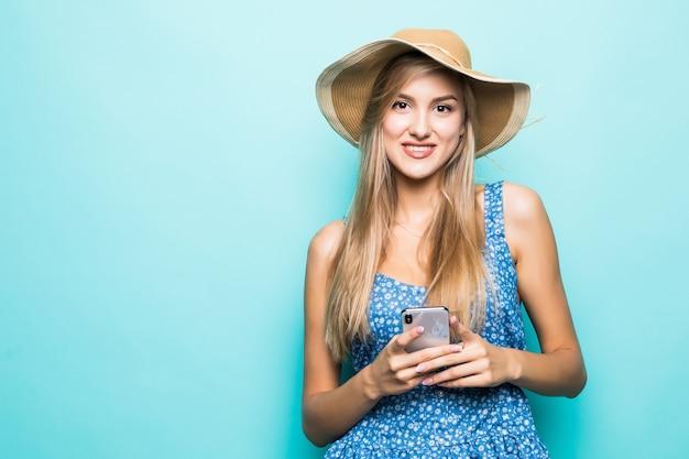 Uśmiechnięta Kobieta Moda Używa Smartfona Na Sobie Słomkowy Kapelusz Na Niebieskim Tle Darmowe Zdjęcia