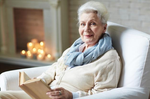 Uśmiechnięta Kobieta Na Emeryturze Czytanie Książki Darmowe Zdjęcia