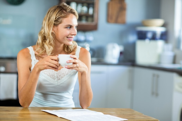 Uśmiechnięta kobieta patrzeje daleko od w domu Premium Zdjęcia