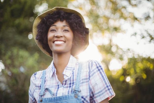 Uśmiechnięta Kobieta Patrzeje Daleko Od W Ogródzie Premium Zdjęcia