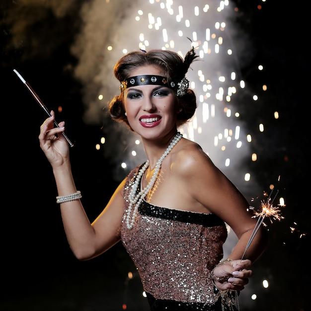 Uśmiechnięta kobieta patrzy na aparat z tłem fajerwerków Darmowe Zdjęcia