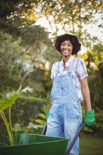 Uśmiechnięta Kobieta Pcha Wheelbarrow W Ogródzie Premium Zdjęcia