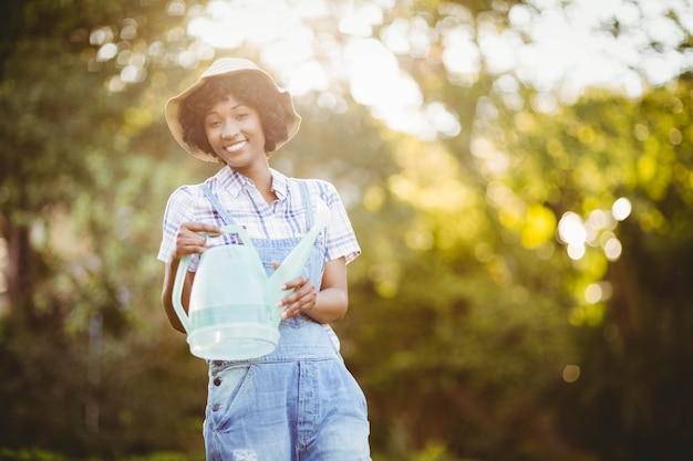 Uśmiechnięta Kobieta Podlewania Roślin W Ogrodzie Premium Zdjęcia