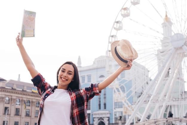 Uśmiechnięta kobieta podniosła rękę z mapą gospodarstwa i kapelusz stojący w pobliżu diabelski młyn Darmowe Zdjęcia