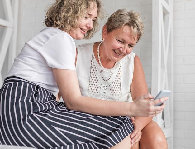 Uśmiechnięta kobieta pokazuje coś od telefonu komórkowego do matki Darmowe Zdjęcia