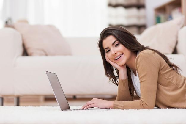 Uśmiechnięta Kobieta Relaksuje W Domu Z Laptopem Darmowe Zdjęcia
