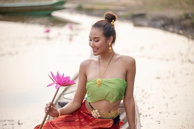 Uśmiechnięta kobieta trzyma lotosu podczas gdy siedzący na łodzi w jeziorze Premium Zdjęcia