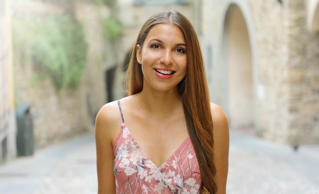Uśmiechnięta Kobieta Ubrana Moda Spaceru Na Ulicach Małego średniowiecznego Miasteczka We Włoszech. Premium Zdjęcia
