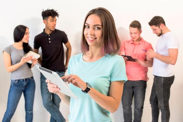 Uśmiechnięta kobieta używa cyfrową pastylkę z jej przyjaciółmi stoi behind Darmowe Zdjęcia