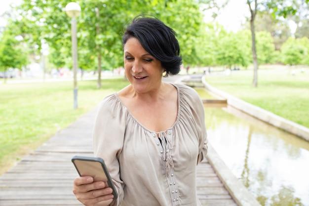 Uśmiechnięta Kobieta Używa Smartphone Outdoors Darmowe Zdjęcia