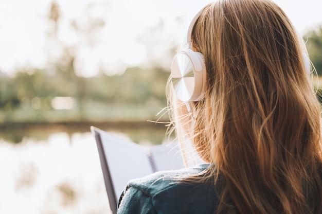 Uśmiechnięta Kobieta W Eyeglasses Czytelniczej Książce I Słuchaniu Muzyka Z Hełmofonami W Parkowy Plenerowym Przeciw światłu Słonecznemu, Miasto Stylu życia Pojęcie. Premium Zdjęcia