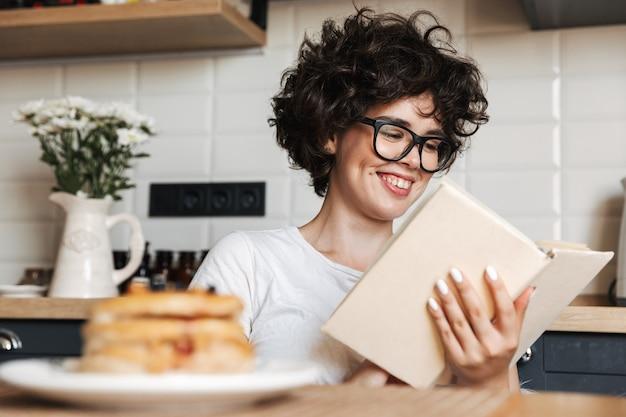 Uśmiechnięta Kobieta Wesoły Smaczne śniadanie Siedząc W Kuchni W Domu, Czytając Książkę Premium Zdjęcia