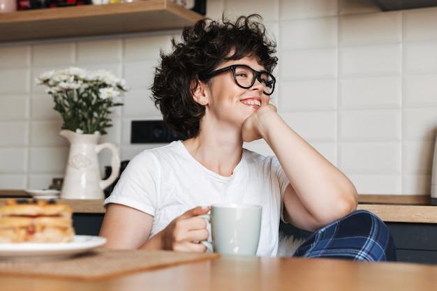 Uśmiechnięta Kobieta Wesoły Smaczne śniadanie Siedząc W Kuchni W Domu, Pijąc Kawę Premium Zdjęcia