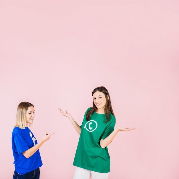 Uśmiechnięta kobieta wskazuje przy jej przyjacielem wzrusza ramionami na różowym tle Darmowe Zdjęcia
