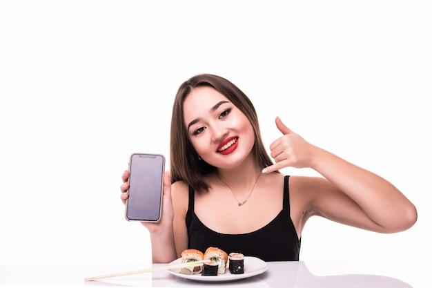 Uśmiechnięta Kobieta Z Czarnymi Włosami I Czerwonymi Ustami Smakuje Bułki Suushi Trzymając W Ręku Drewniane Pałeczki Rozmawia Przez Telefon Darmowe Zdjęcia