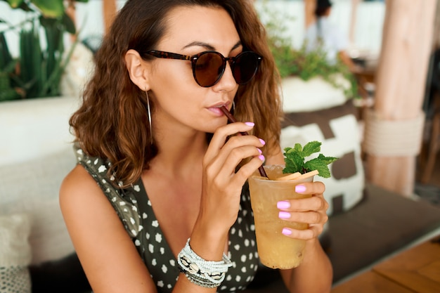 Uśmiechnięta Kobieta Z Kręconymi Włosami W Modnym Letnim Stroju, Chłodzenie W Przytulnej Kawiarni, Picie Lemoniady. Darmowe Zdjęcia