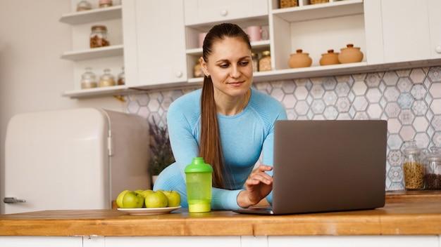 Uśmiechnięta Kobieta Za Pomocą Komputera W Nowoczesnych Wnętrzach Kuchni. Gotowanie I Koncepcja Zdrowego Stylu życia. Kobieta Szuka Przepisu Lub Transmituje Strumieniowo Online Premium Zdjęcia