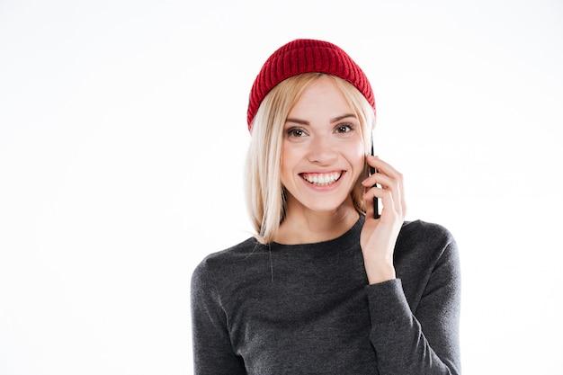Uśmiechnięta ładna Młoda Kobieta Opowiada Na Telefonie Komórkowym W Kapeluszu Darmowe Zdjęcia
