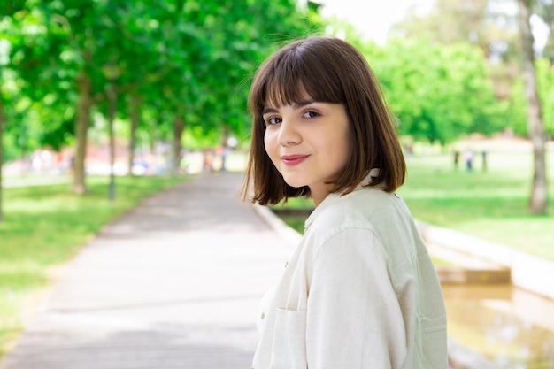 Uśmiechnięta ładna młoda kobieta pozuje przy kamerą w miasto parku Darmowe Zdjęcia