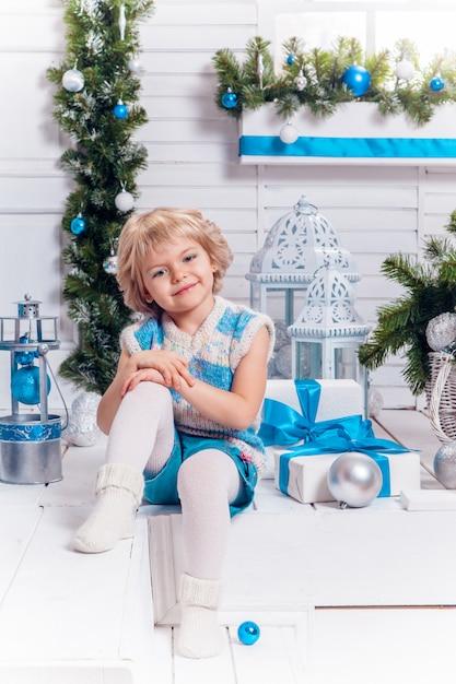 Uśmiechnięta mała blondynka słodka dziewczyna siedzi na werandzie surround Premium Zdjęcia