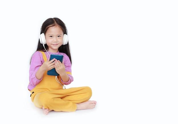 Uśmiechnięta Mała Dziewczynka Cieszy Się Słuchać Muzyka Hełmofonami Premium Zdjęcia