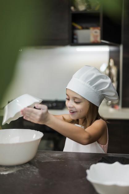 Uśmiechnięta mała dziewczynka miesza składniki w pucharze na kuchennym worktop Darmowe Zdjęcia