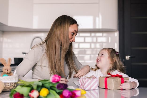 Uśmiechnięta Mama Daje Teraźniejszości Jej Córka Na Jej Urodziny Darmowe Zdjęcia