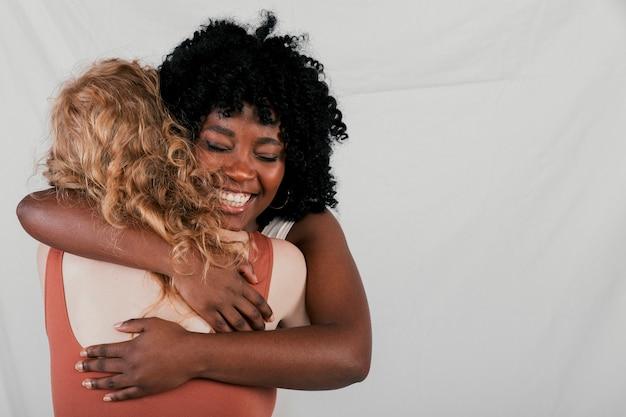 Uśmiechnięta młoda afrykańska kobieta ściska jej caucasian żeńskiego przyjaciela przeciw popielatemu tłu Darmowe Zdjęcia