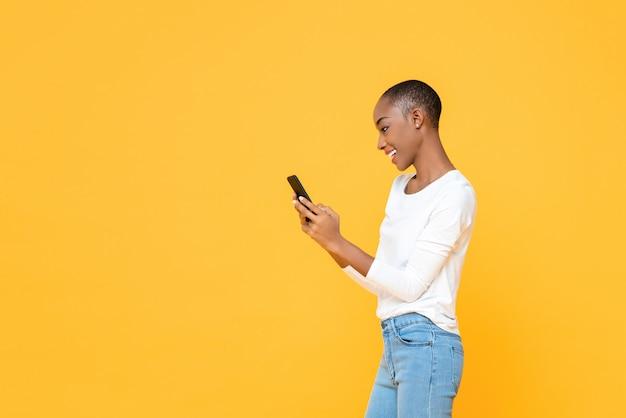 Uśmiechnięta Młoda Amerykanin Afrykańskiego Pochodzenia Kobieta Używa Smartphone Odizolowywającego Na Kolor żółty ścianie Premium Zdjęcia