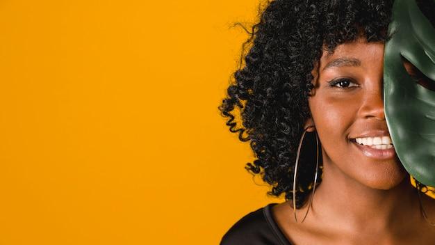 Uśmiechnięta Młoda Amerykanin Afrykańskiego Pochodzenia Kobieta Z Liściem Na Barwionym Tle Darmowe Zdjęcia