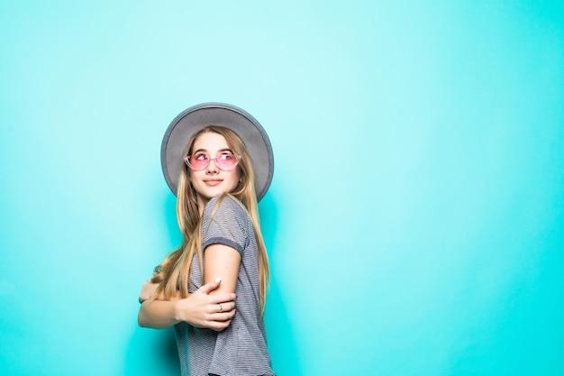 Uśmiechnięta Młoda Dziewczyna Moda T-shirt, Kapelusz I Okulary Przezroczyste Na Białym Tle Na Zielonym Tle Darmowe Zdjęcia