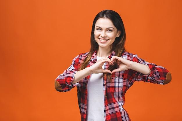 Uśmiechnięta Młoda Dziewczyna W Przypadkowym Pokazuje Sercu Z Dwa Rękami, Miłość Znak. Pojedynczo Na żółtym Tle. Premium Zdjęcia