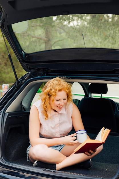 Uśmiechnięta Młoda Kobieta Czytanie Książki W Podróży Darmowe Zdjęcia