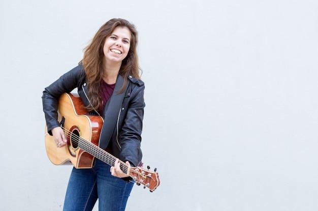 Uśmiechnięta Młoda Kobieta Gra Na Gitarze Darmowe Zdjęcia
